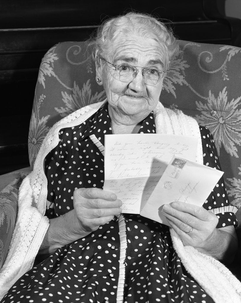 Detail of 1960s elderly woman in polka-dotted dress & shawl reading letter by Corbis