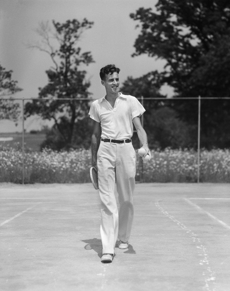 Detail of 1930s man walking across tennis court holding tennis racket & balls by Corbis