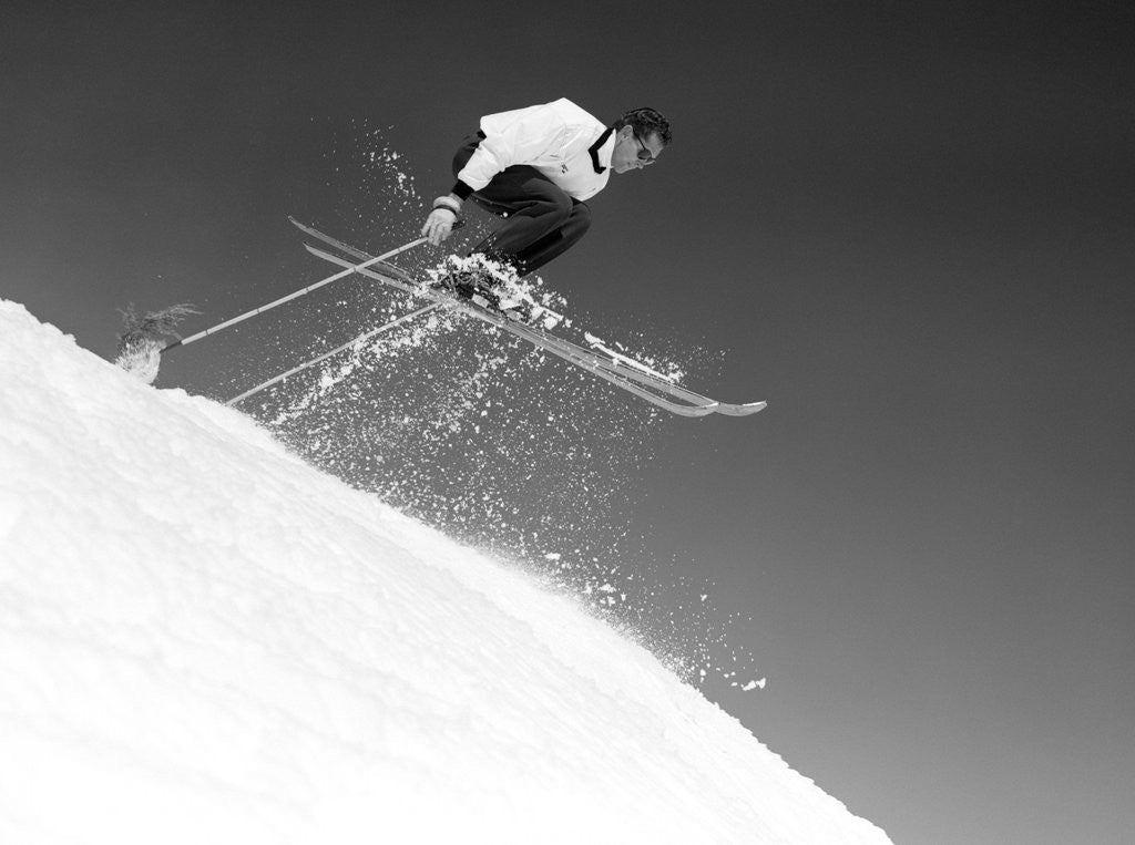 Detail of 1950s man skier skiing down slope jumping into air by Corbis