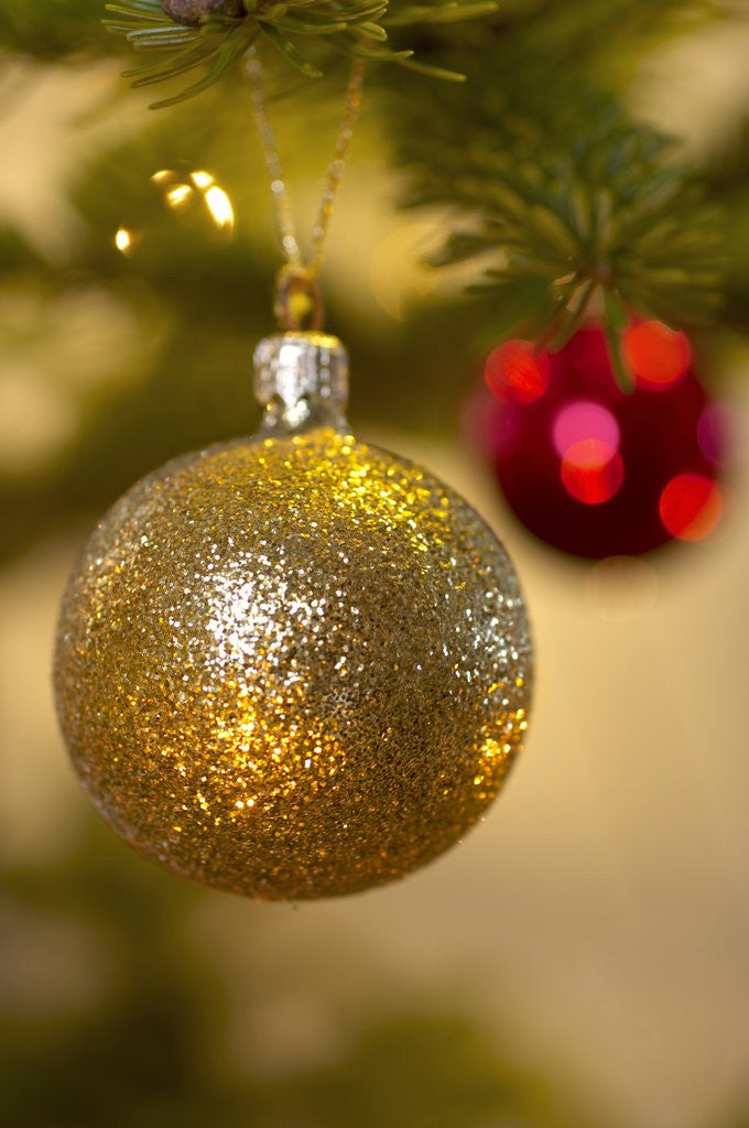 Detail of Close-up of a golden hanging Christmas bauble on blurred tree by Corbis