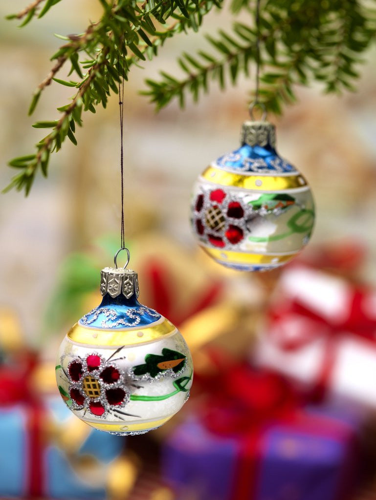 Detail of Close-up of decorated hanging baubles against blurred gifts in the background by Corbis