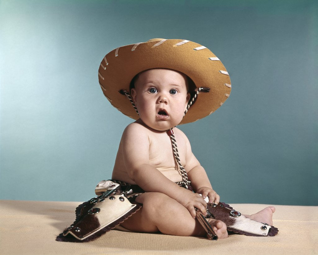 Detail of 1960s Baby Wearing Cowboy Costume With Funny Facial Expression Looking At Camera by Corbis
