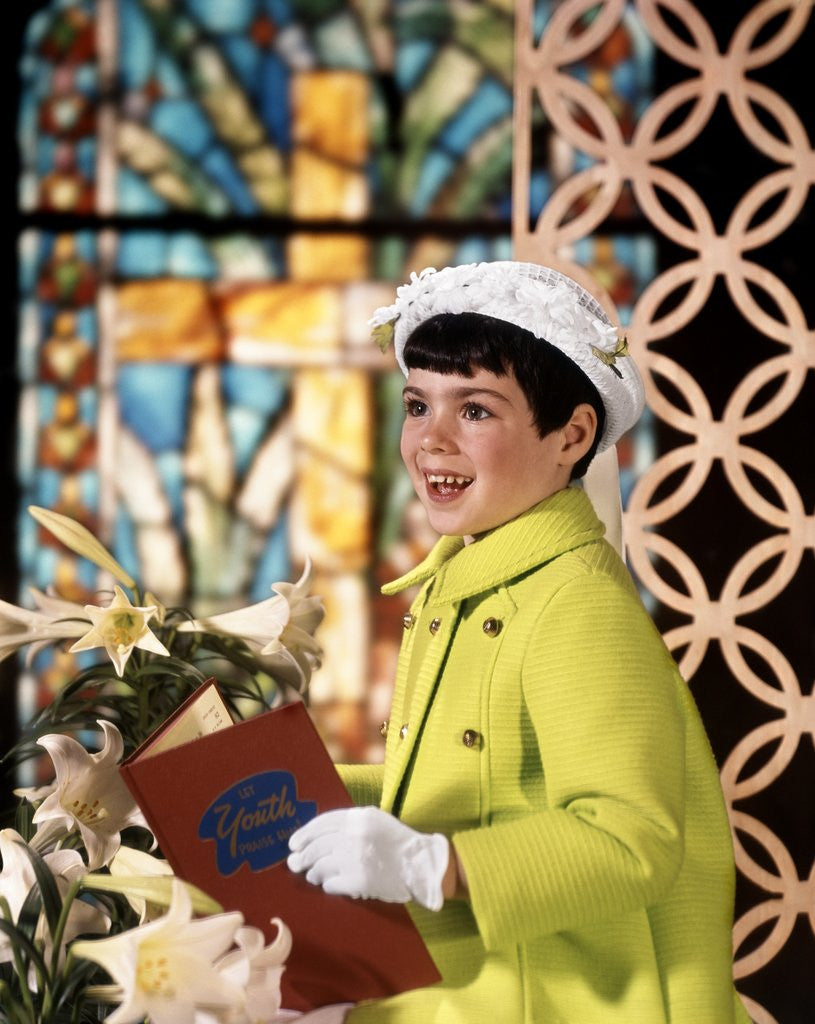 Detail of 1960s Smiling Happy Young Girl Easter Sunday Clothes Green Coat White Bonnet Hat Gloves Holding Church Hymnal by Corbis