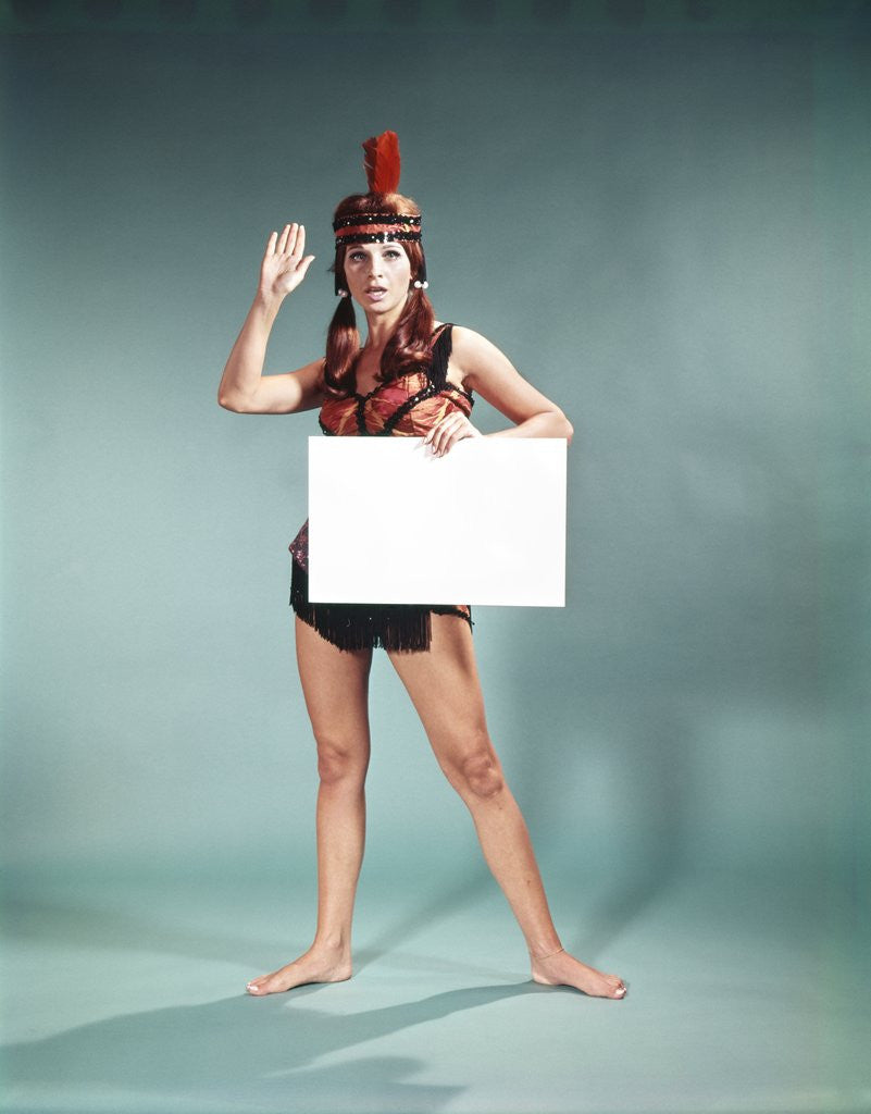 Detail of 1960s 1970s Character Woman Wearing Native American Feather Headdress Making How Gesture Holding Blank Sign Looking At Camera by Corbis