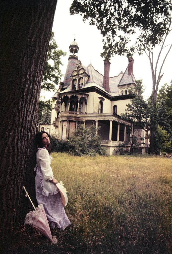 Detail of 1960s 1970s Woman Standing Beside Tree Front Of Abandoned Haunted Victorian House by Corbis