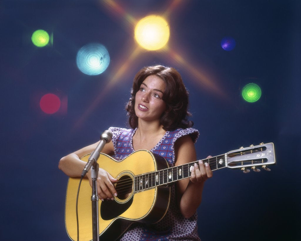Detail of 1970s Woman Girl Performer Playing Guitar Singing Microphone Stage Lights by Corbis