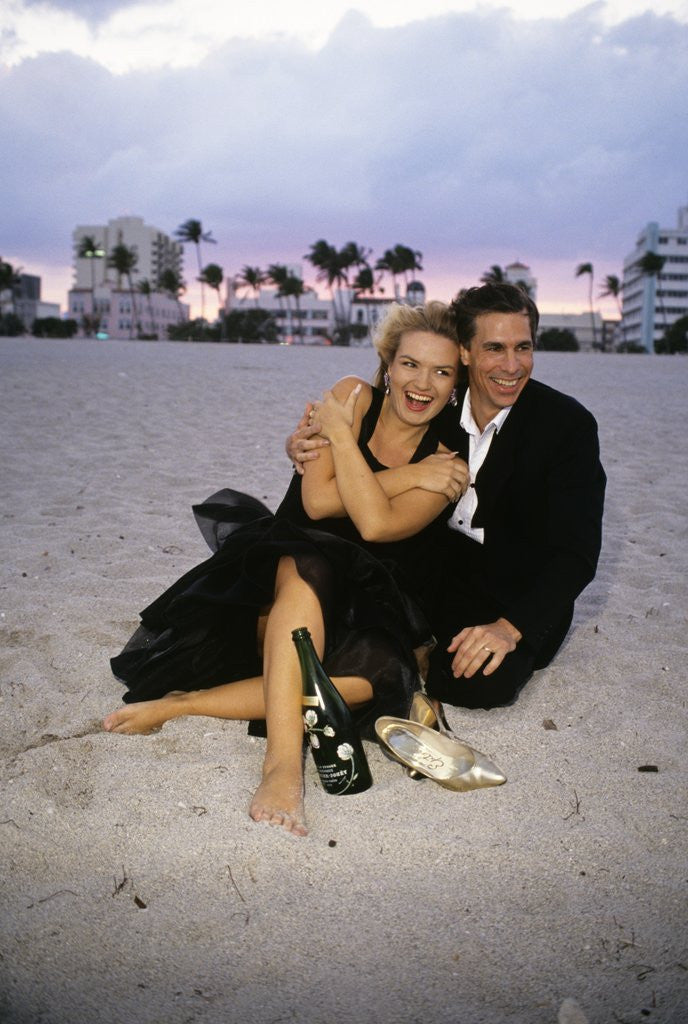 Detail of 1990s Laughing Couple Man Woman In Formal Wear Sitting Hugging On Beach by Corbis