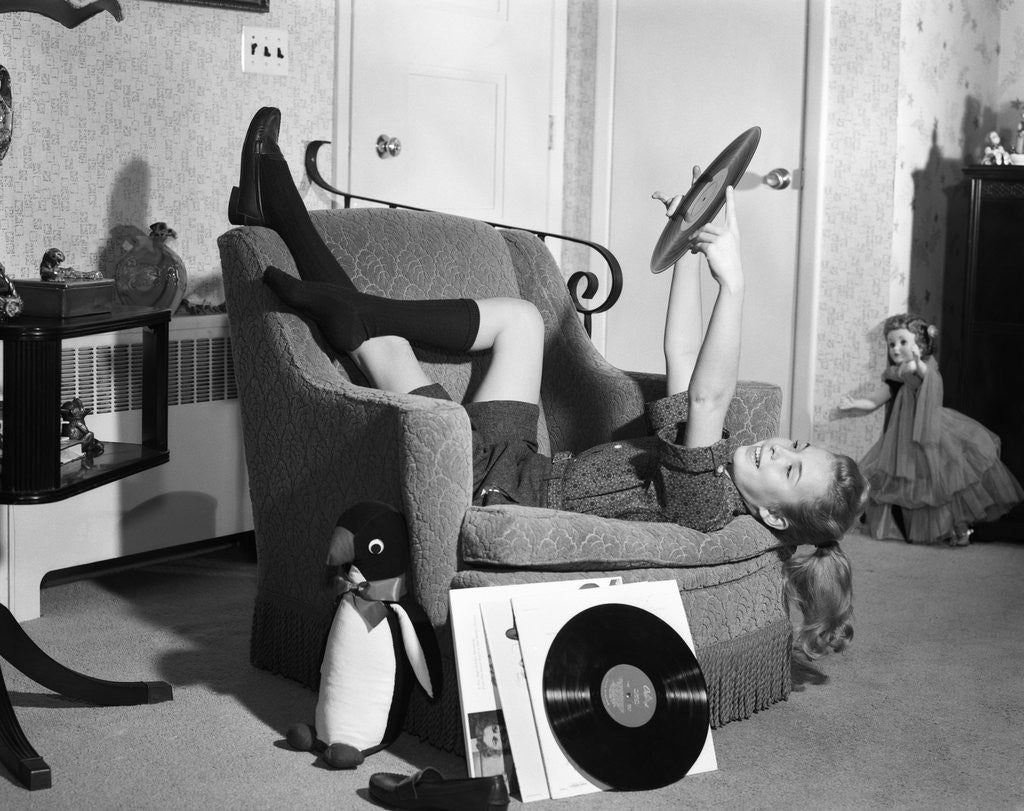 Detail of 1950s 1960s Teenage Girl Smiling Reclining Upside Down On Chair Holding Vinyl Record Album Listening To Music by Corbis