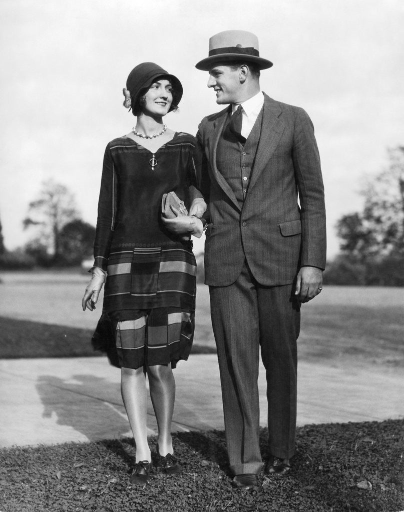 Detail of 1920s Portrait Smiling Stylish Couple Walking Arm In Arm by Corbis