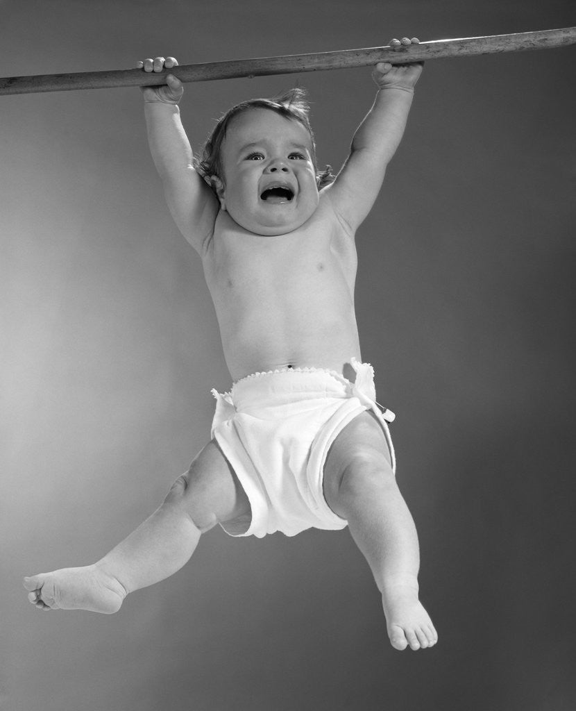 Detail of 1960s Baby Hanging From Rod With Frightened Expression On Verge Of Tears by Corbis