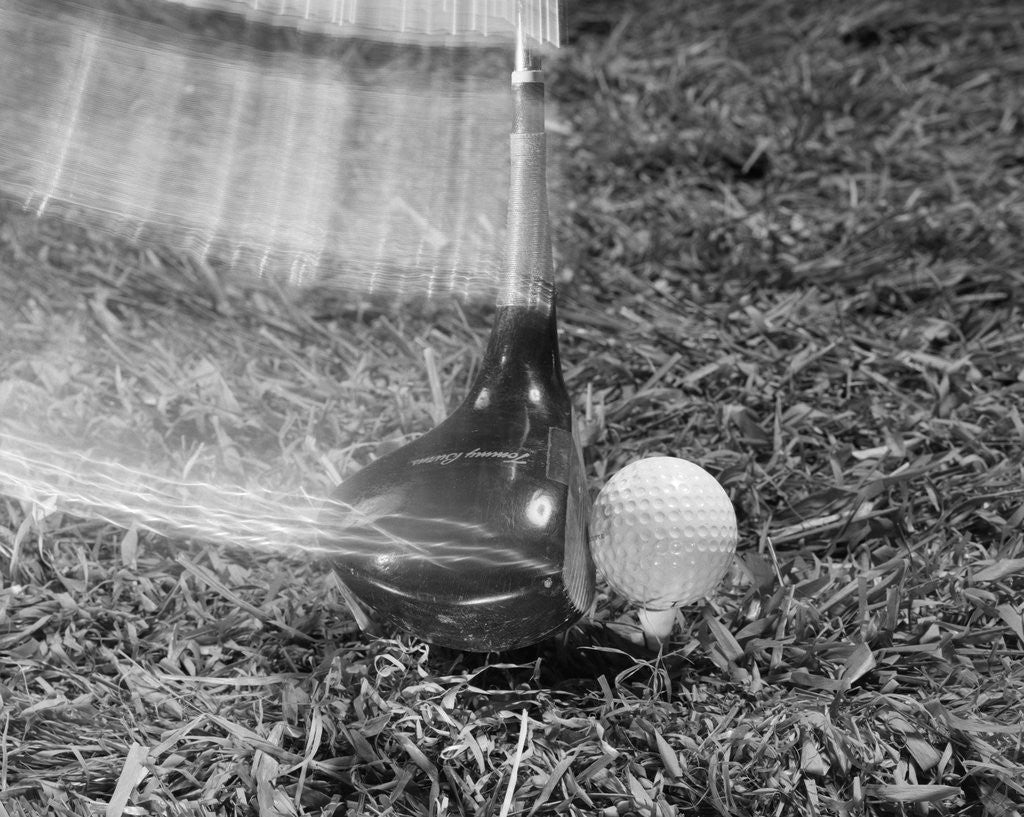 Detail of 1960s Moving Driver Golf Club Hitting Ball On Tee In Grass by Corbis