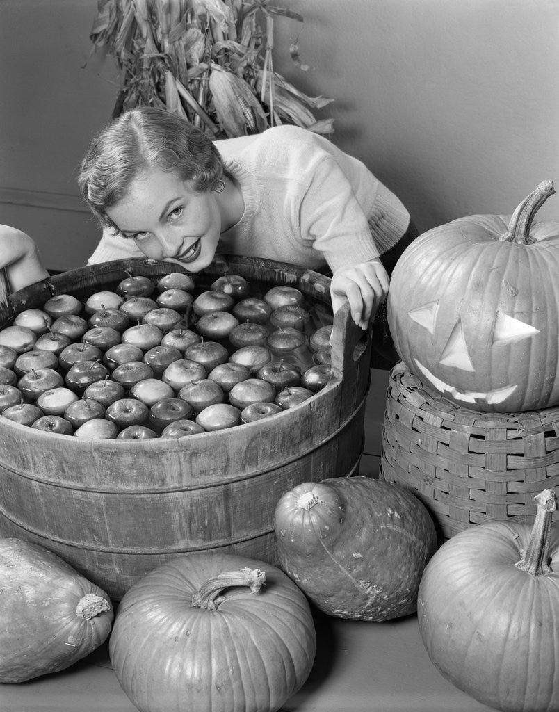 Detail of 1950s Smiling Woman Leaning Over Wooden Tub Filled With Water About To Begin Bobbing For Apples by Corbis