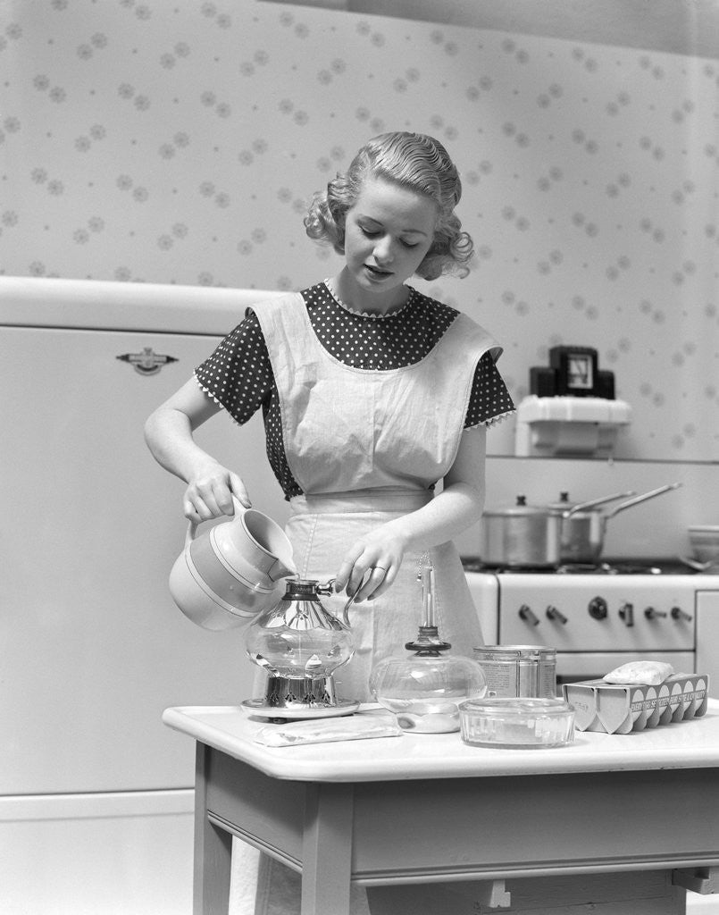 Detail of 1930s Woman In Kitchen Wearing Apron Making Breakfast Pouring Water Into Coffee Pot by Corbis