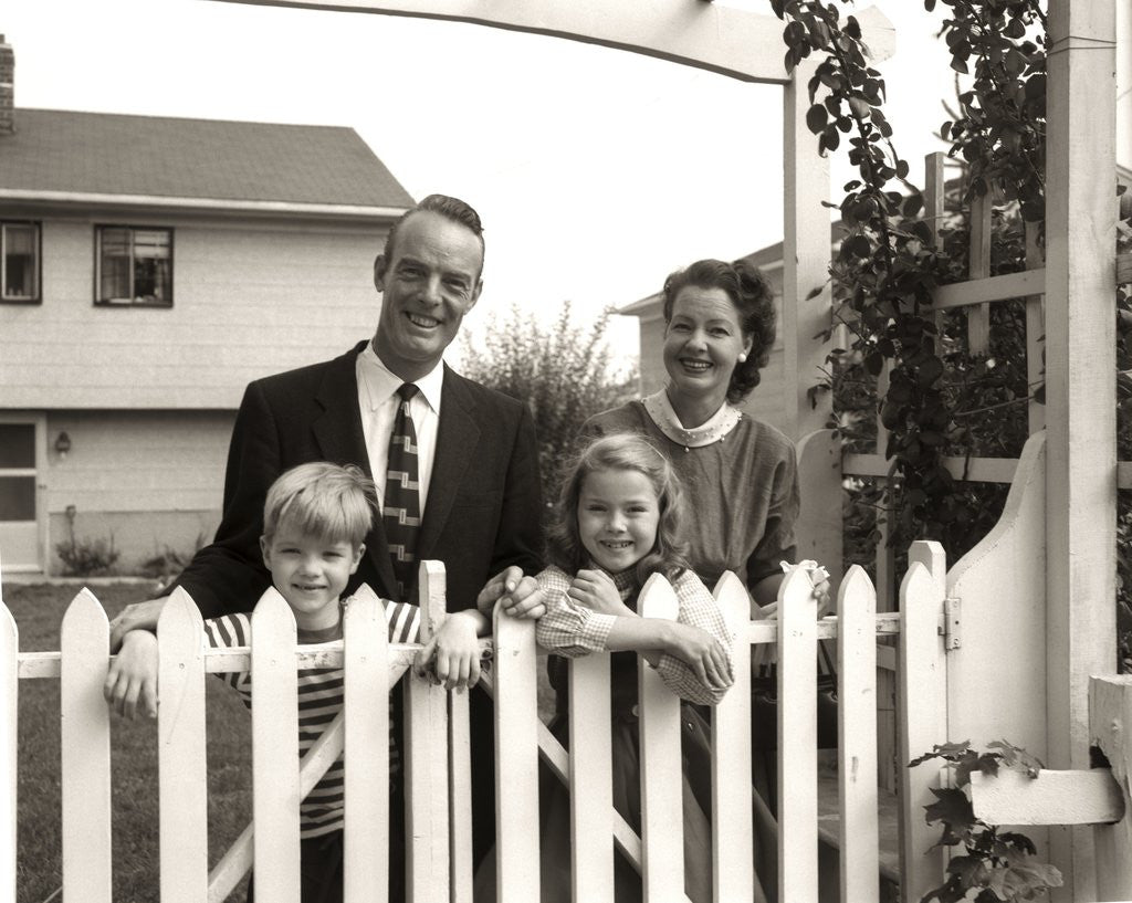 Detail of 1950s family of four behind picket fence by Corbis