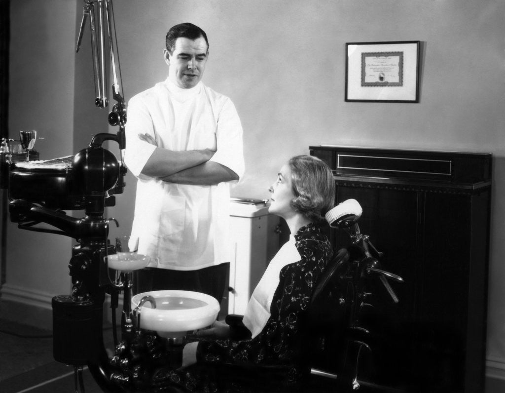 Detail of 1930s 1940s dentist speaking with a female patient by Corbis