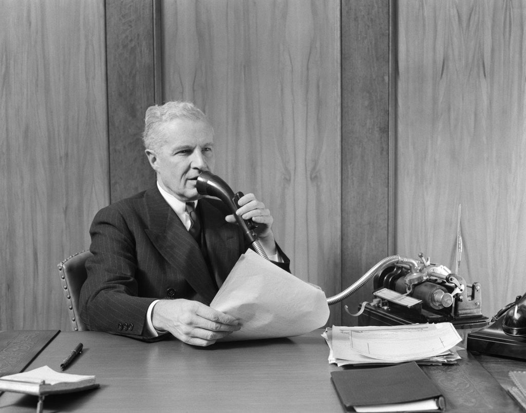 Detail of 1930s senior executive speaking into a dictaphone by Corbis