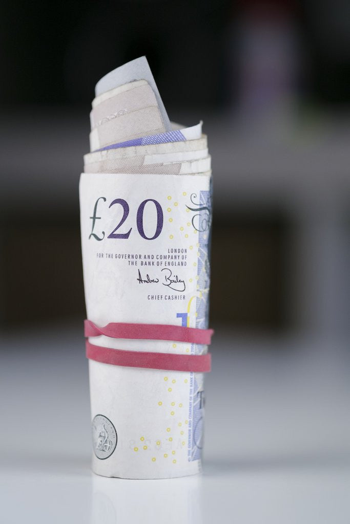 Detail of A roll of twenty pound notes on a table by Corbis