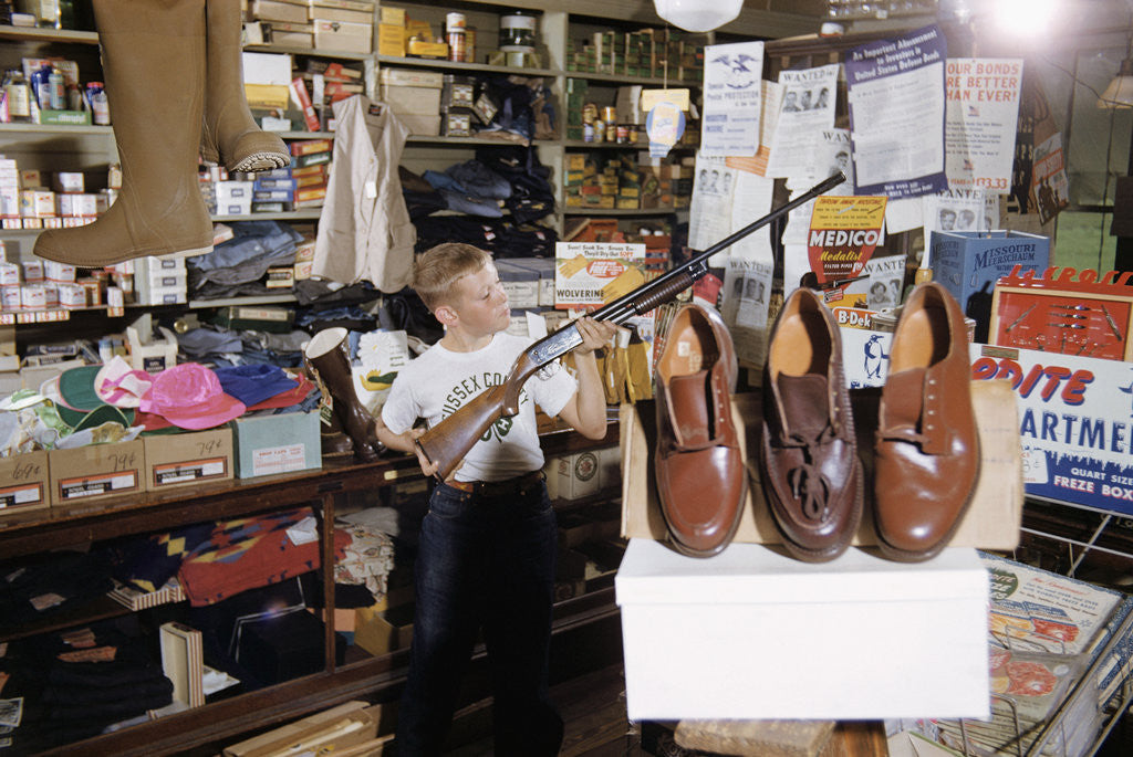 Detail of Boy Holding Shotgun in Sporting Goods Store by Corbis