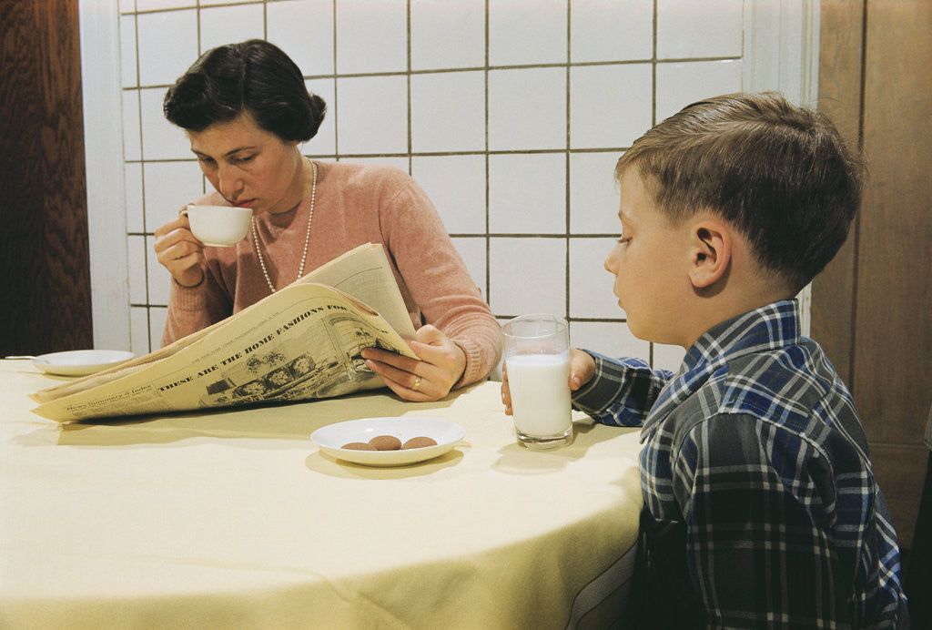 Detail of Boy Eating Cookies and Milk as Mom Reads by Corbis