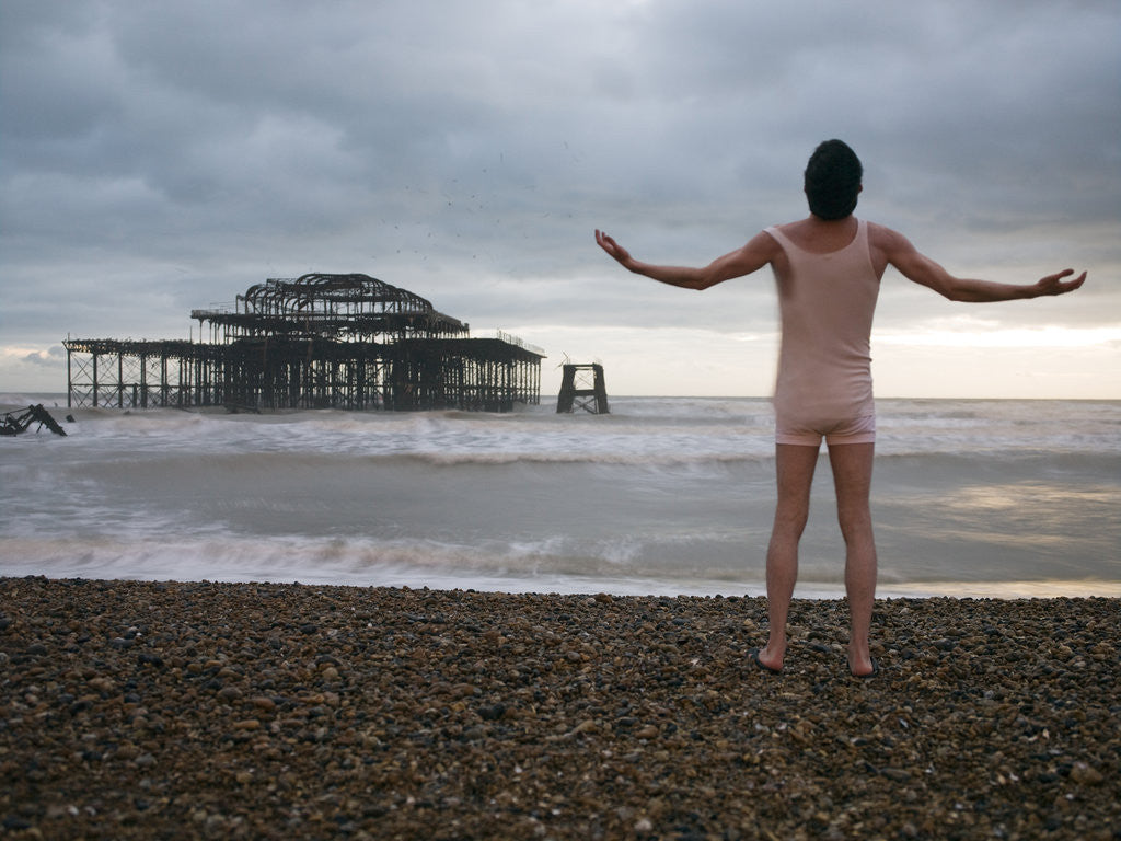 Detail of Man standing on beach with outstretched hands, rear view, Brighton by Assaf Frank