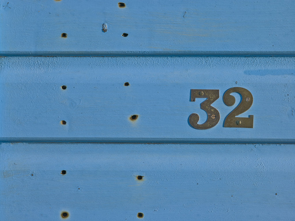Detail of 32 Number Sign on Beach hut close-up, Blue Background by Assaf Frank