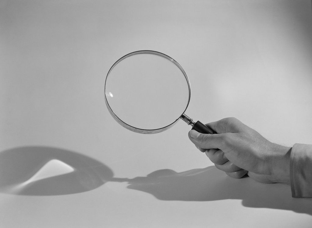 Detail of Hand Holding a Magnifying Glass by Corbis