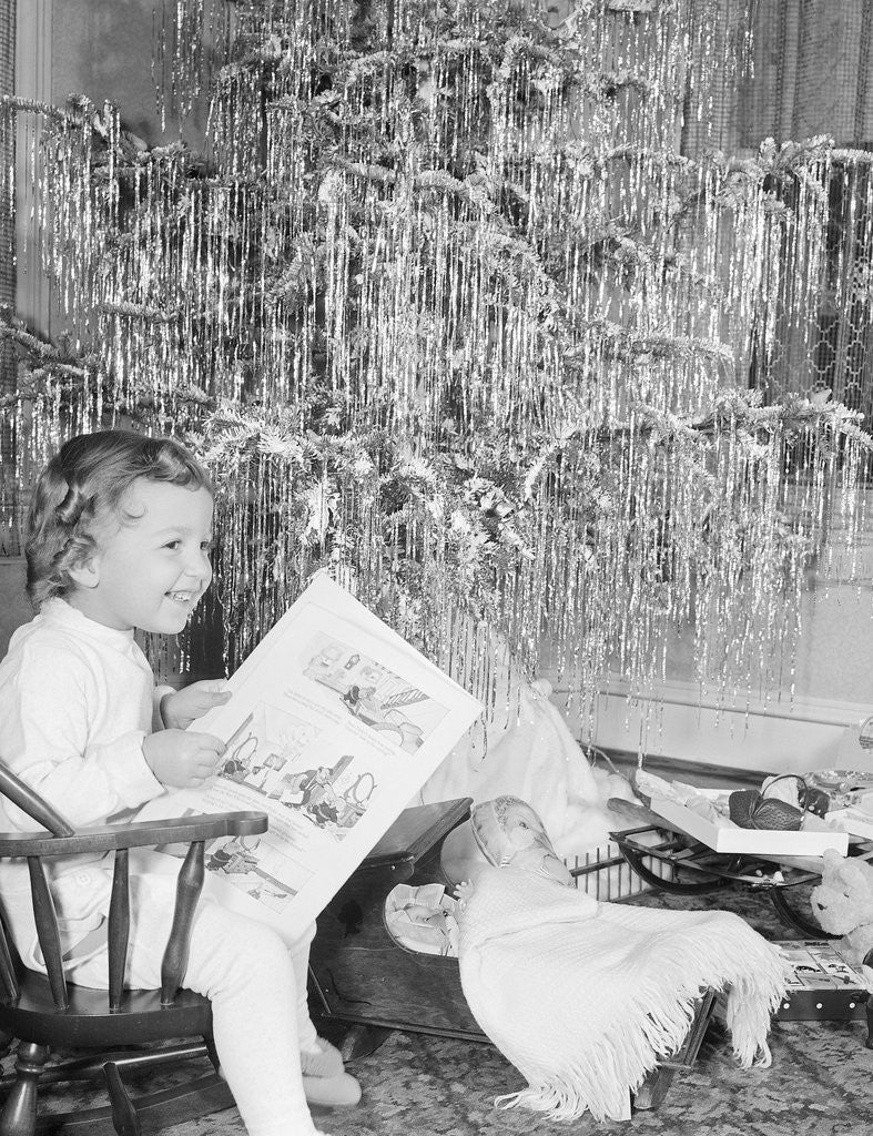 Detail of Girl Sitting Beside Christmas Tree by Corbis