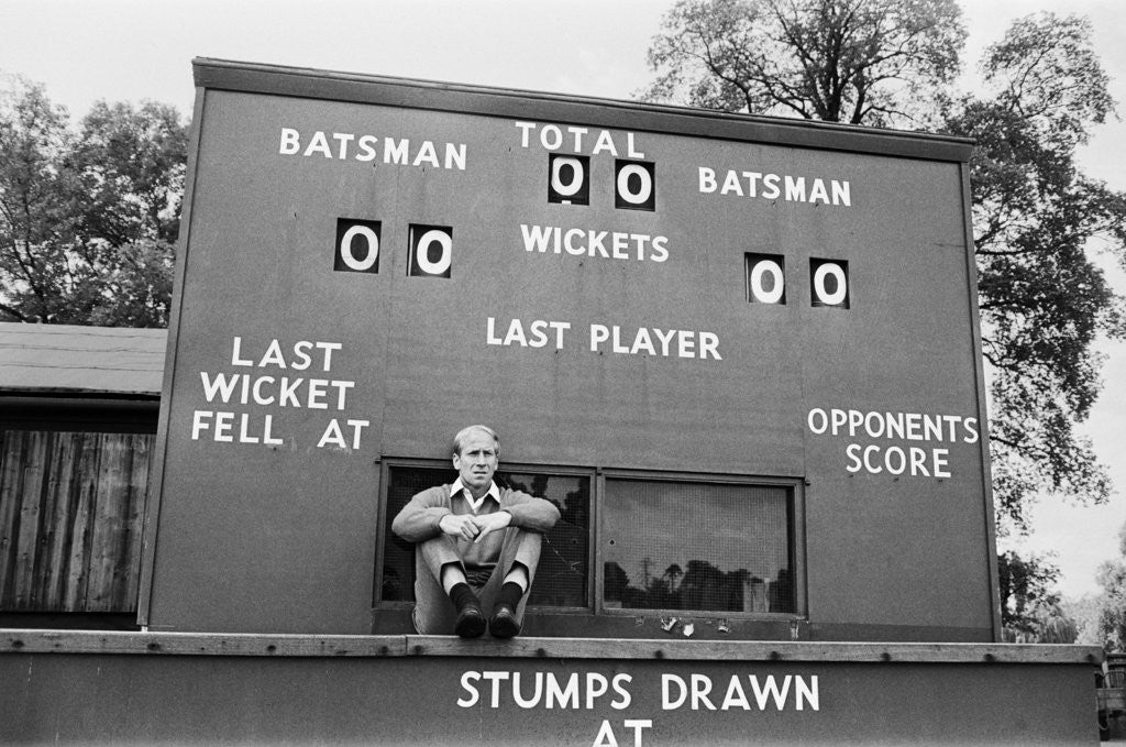 Detail of Bobby Charlton sits in front of a cricket scoreboard by Anonymous