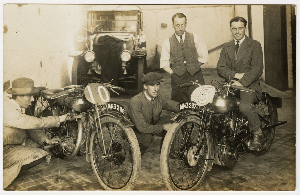 Detail of Tom Sheard, TT (Tourist Trophy) rider poses with machine number 13 (registration MN3297) in a garage with mechanics by Thomas Horsfell Midwood