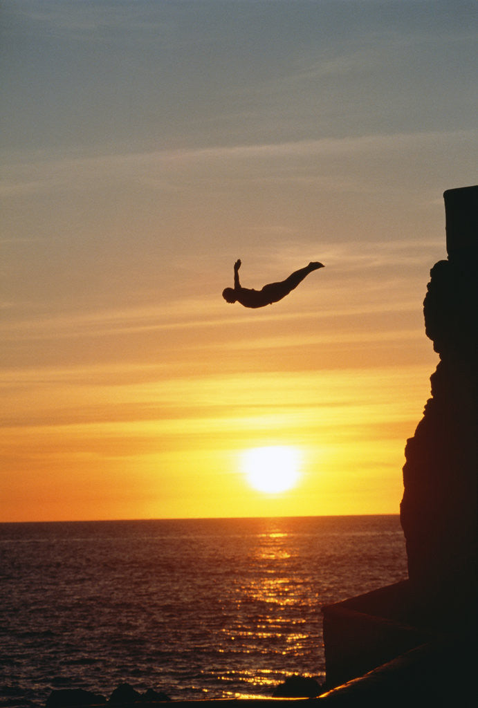 Detail of Cliff Diver Above Setting Sun by Corbis
