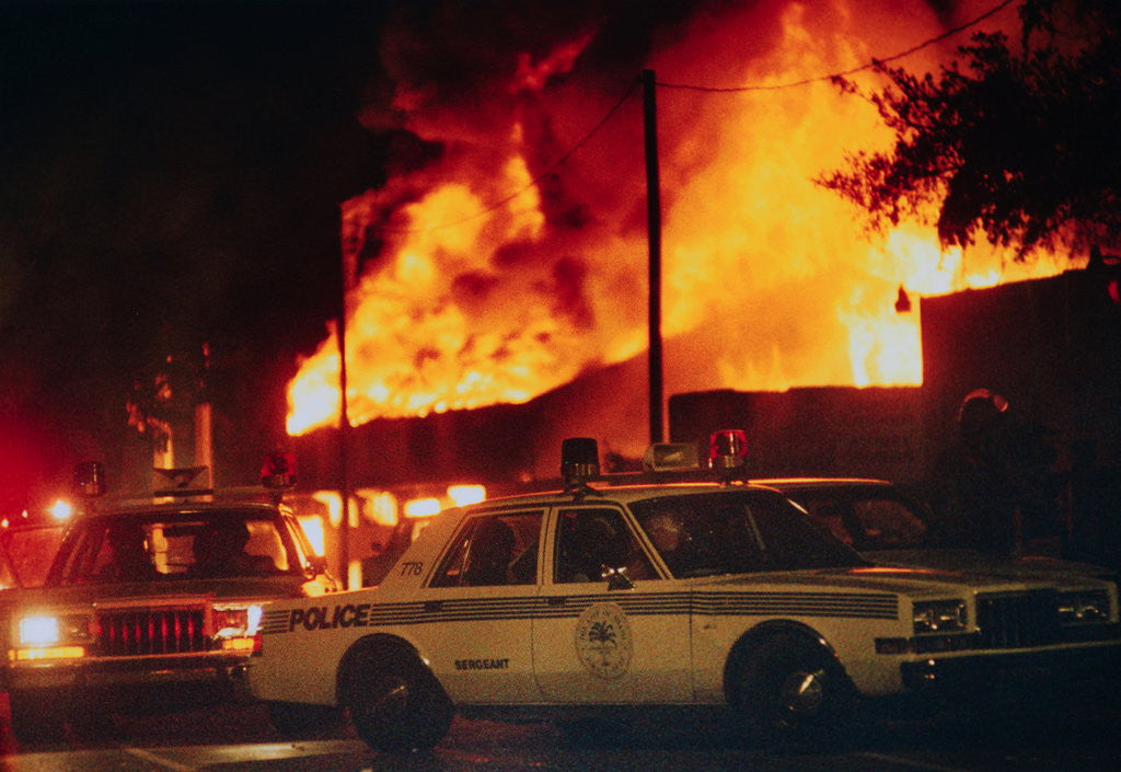 Detail of Burning Buildings with Police on the Scene by Corbis