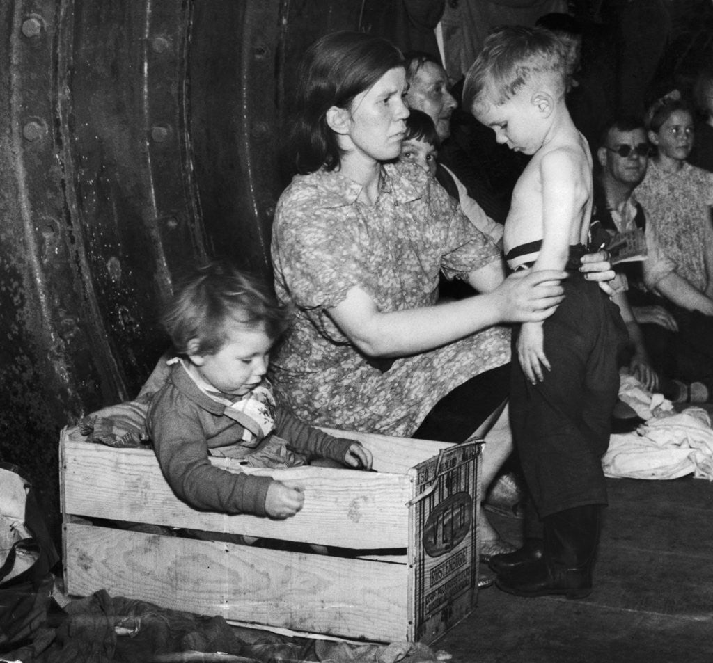Detail of A mother tends to her young son in an underground bomb shelter during an air raid by Staff