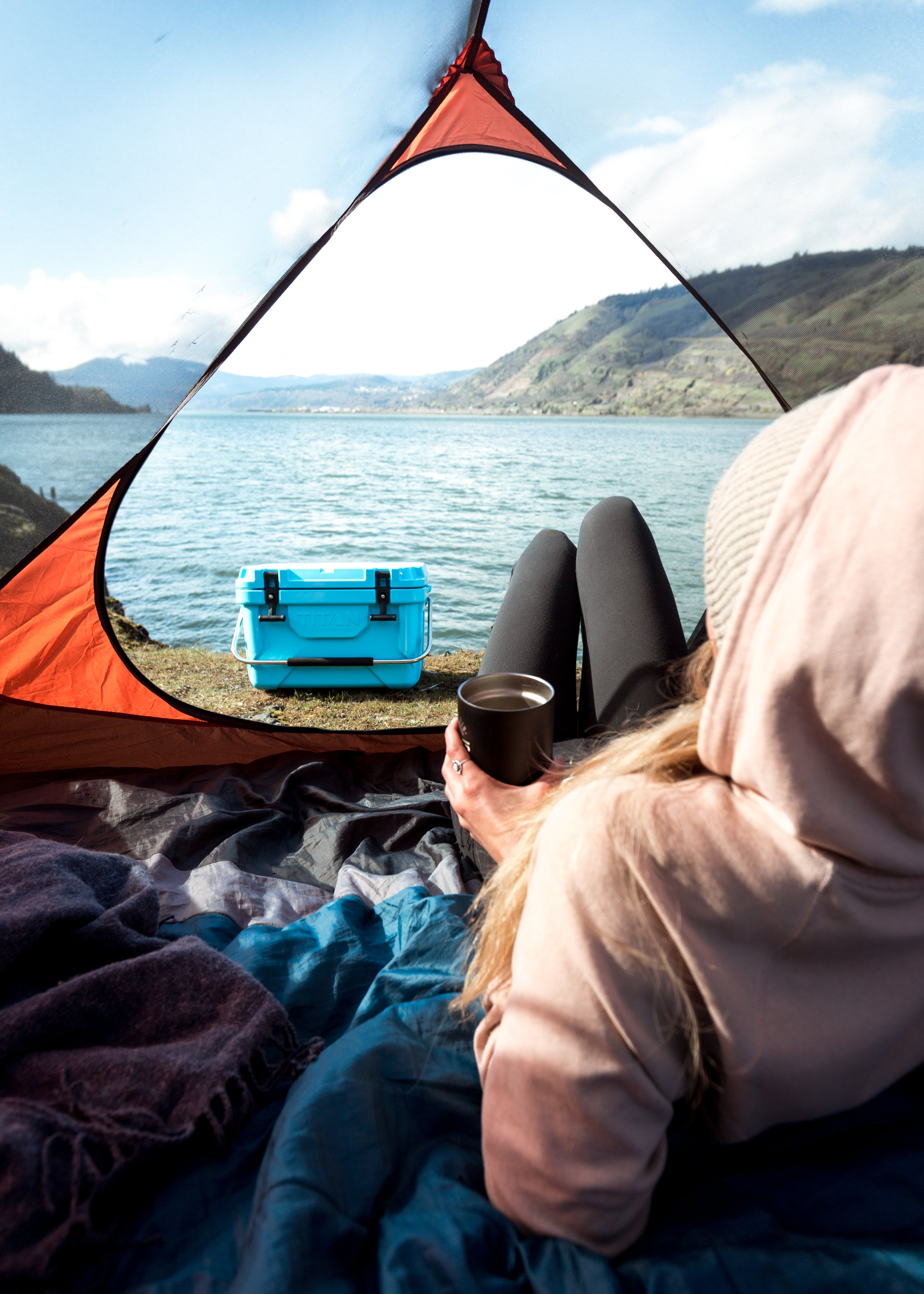 Camping with Arctic Zone - carrying the cooler past the tent - chilling in the tent with a drink overlooking a lake - Best coolers for camping