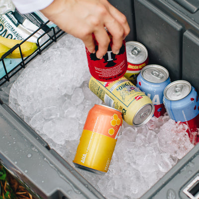 Titan Deep Freeze® 55Q Premium Ice Chest - Gray - Lifestyle, grabbing a drink from the ice filled cooler