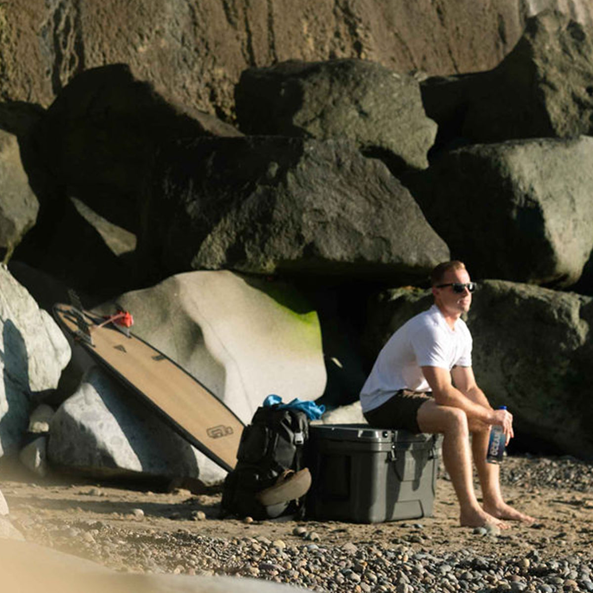 Titan Deep Freeze® 55Q Premium Ice Chest - Gray - Lifestyle, taking a break on the cooler at the beach