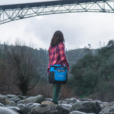 Titan Deep Freeze® 24 Can Bucket Tote - Blue - Lifestyle, hiking underneath a bridge