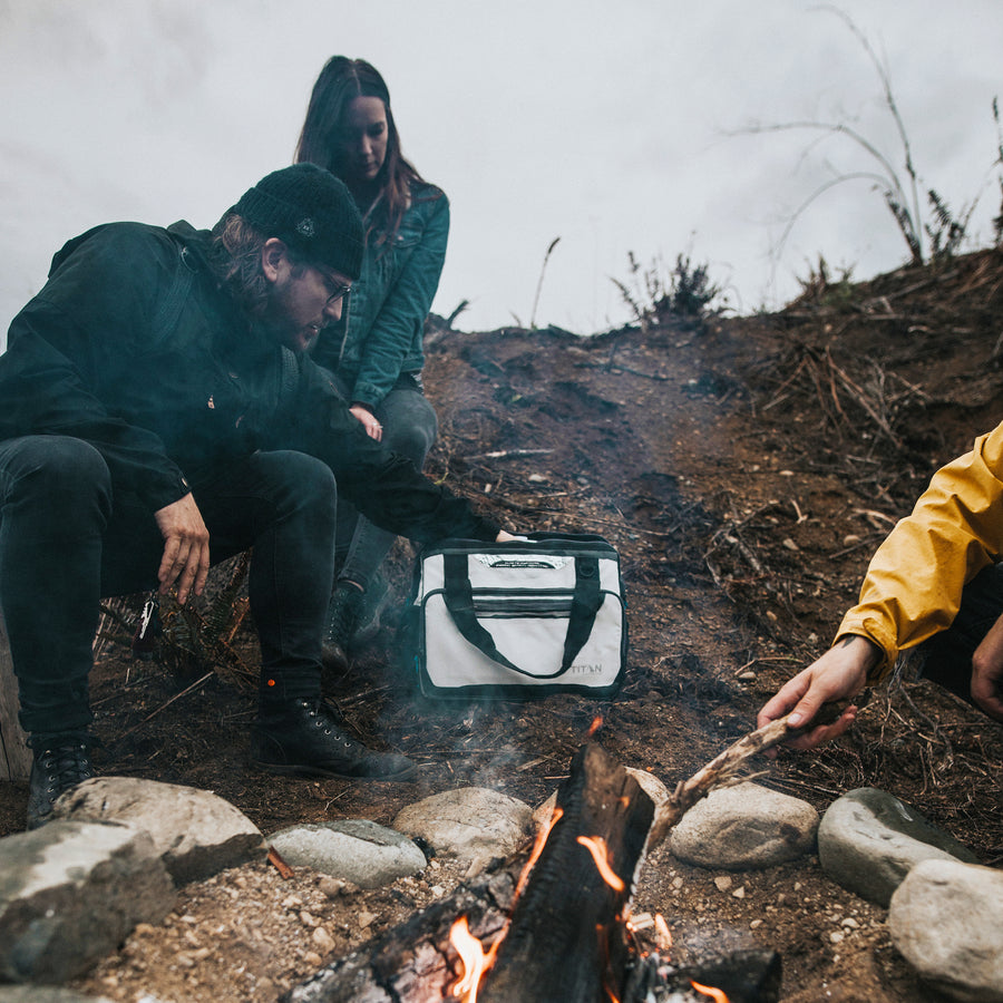 40 Can Titan Deep Freeze® Duffel - lifestyle - by the camp fire