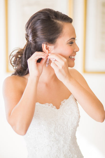 Bride putting on her earrings on wedding day