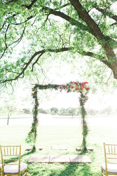 Outdoor Wedding Ceremony with a flower arch, under large tree on golf course