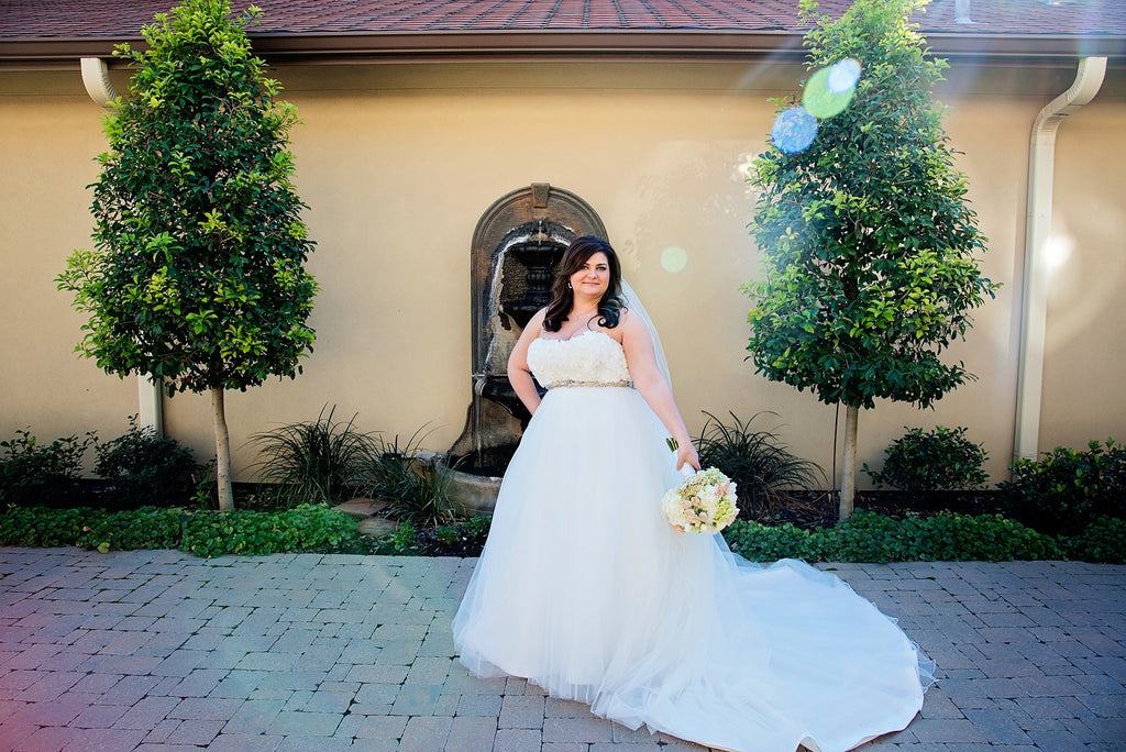 Bride standing outside near a fountain