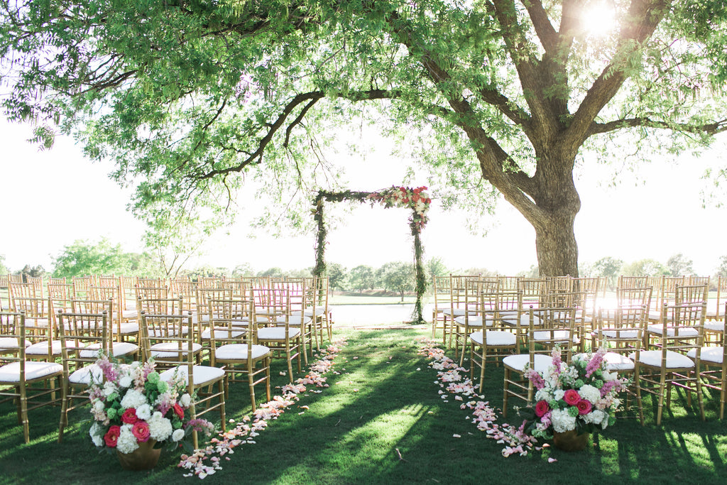 Outdoor wedding ceremony with large tree and flower arch with gold chivari chairs