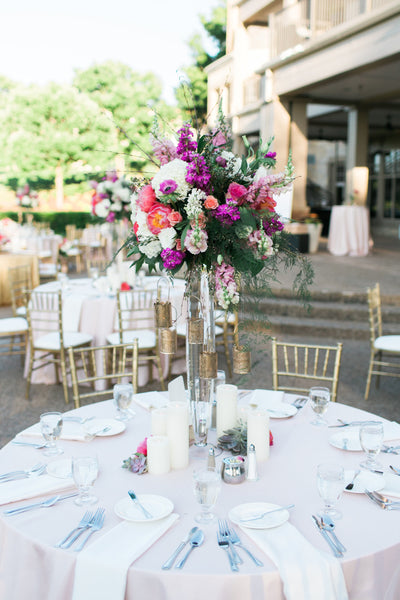 Tall wedding centerpiece for outdoor wedding reception with pink and purple flowers with gold accents