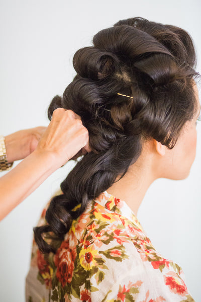Bride getting her hair done on wedding day, wearing a flower robe