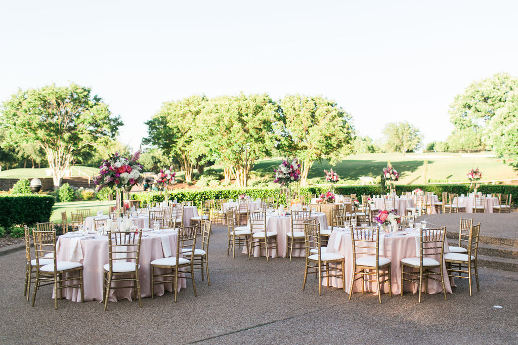 outdoor wedding reception soft pink flowers gold chairss