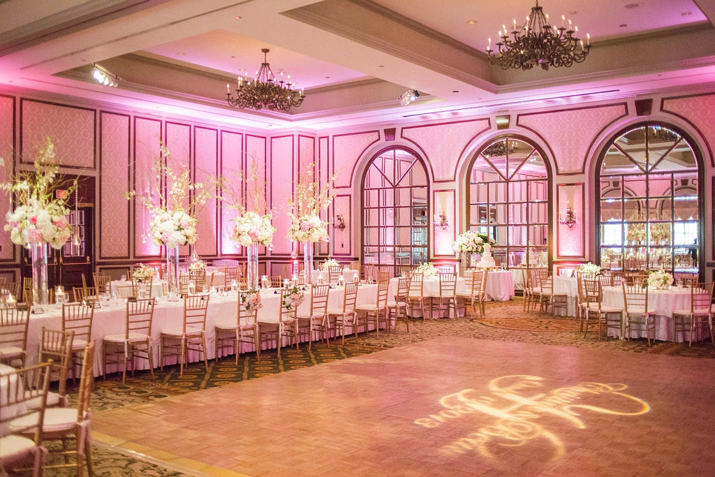 Pink wedding reception with a light monogram on the dance floor
