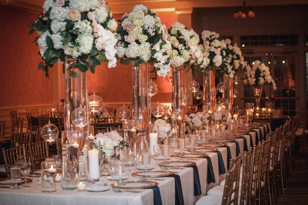 Tall white wedding centerpieces with white sequin linens and lots of candles, navy blue napkins