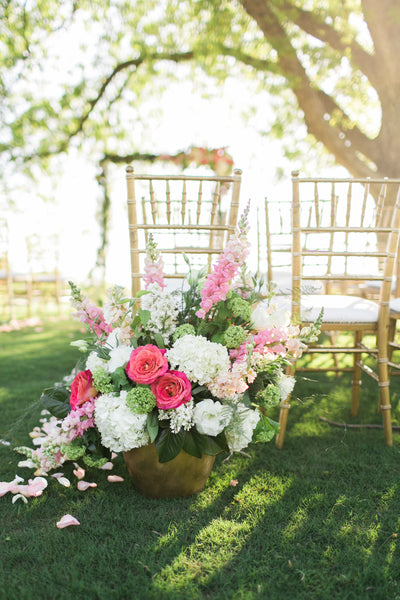 Outdoor wedding ceremony with blush, pink, purple and cream flower arrangements