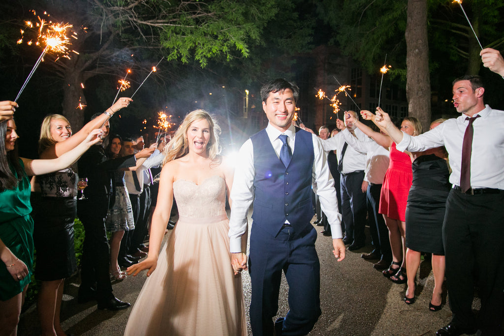 Outdoor wedding exit with sparklers, bride in a blush wedding dress, groom in custom suit