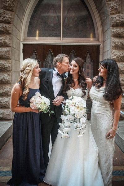 Bride and her family on wedding day, tux, navy bridesmaid dress, metallic mother of the bride dress