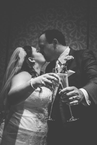 Bride and groom kissing with a toast of champagne glasses in their hands